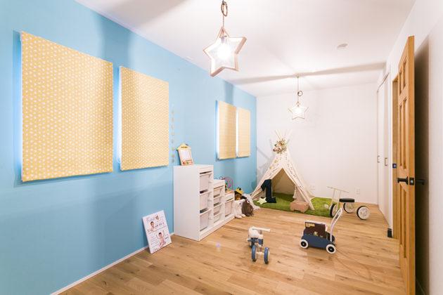 テーマカラーであるブルーの壁紙と可愛い星型照明がある子供部屋。