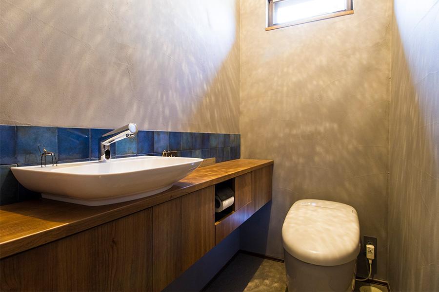 青いタイルと照明の陰影がトイレを安らぎの空間に。