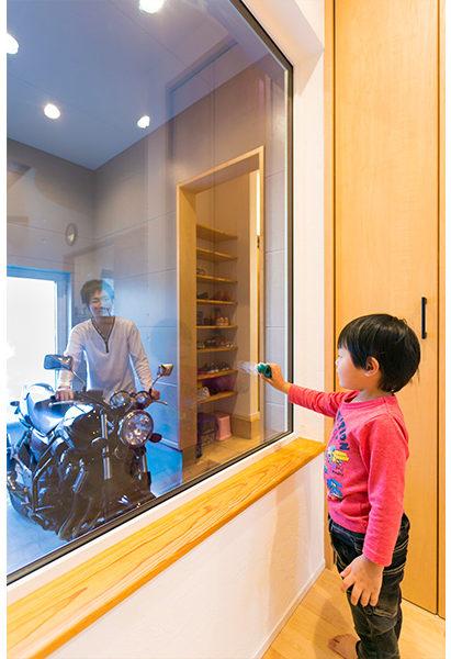 ガラス越しに見えるバイクガレージ。機械いじりをする親父の背中はかっこいい