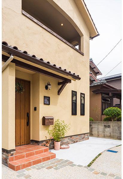 外壁は黄色い塗り壁で仕上げスッキリ三角屋根のお家です