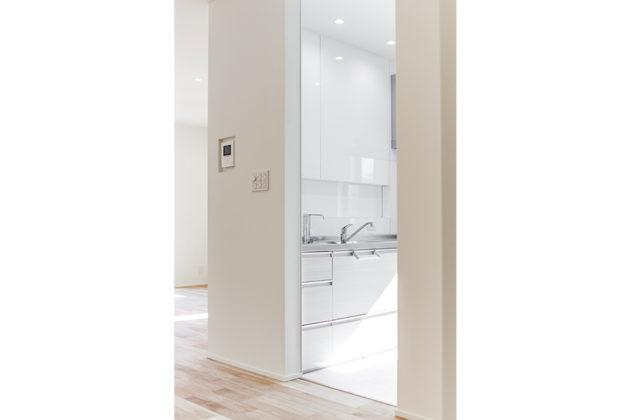 半独立型のキッチン。白でまとめた清潔感溢れる空間