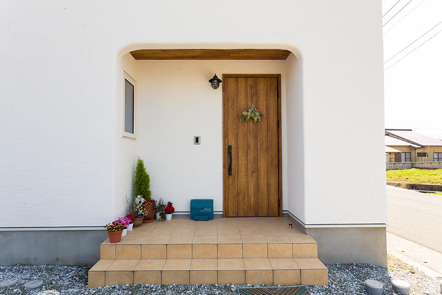 白い塗り壁に木の玄関ドア